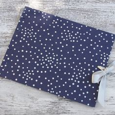 Wedding Guest Book Silver Stars on Navy Blue by EmersonBindery. Silver stars glistening on a navy blue background. Ties closed with a platinum silver ribbon. Handmade in NC. Available on Etsy.