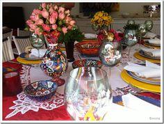 A toalha vermelha foi suavizada com a renda branca, dando destaque aos adornos decorativos coloridos. Flores deixam o espaço mais romântico e sensual. Imagem: Diário da Micha