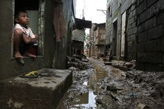 A boy looks out of his home in a low lying community, Aug. 12, 2012, Manila, Philippines. Courtesy boston.com