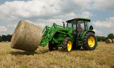5E tractor picking up a hay bale