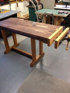 Partially completed woodworking bench of laminated walnut on top supported on red oak legs and frame