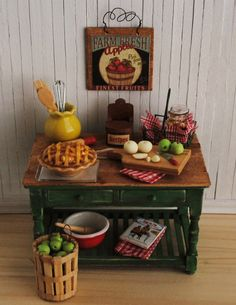 Miniature Farmhouse Baking Table In A Beautiful Green Color With Wood Plank Top, Apple Pie, Recipe Box, Bushel Basket With Apples, And More. $110.00, via Etsy.