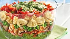 1 package (9 oz) refrigerated cheese-filled tortellini 1 cup Green Giant® frozen sweet peas (from 1-lb bag) 5 cups torn romaine lettuce 1 1/2 cups julienne (matchstick-cut) carrots 2 cups chopped or strips grilled chicken 1 medium red bell pepper, cut into strips 1/2 cup reduced-fat mayonnaise or salad dressing 1/2 cup basil pesto 1/4 cup buttermilk 2 tablespoons chopped fresh parsley or basil leaves
