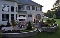 A multi level patio design with raised planters containing specimen plant material with shrubs and perennials providing flower color all season.  The landscape lighting extends the use of the living space even after the sun has set.