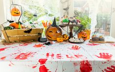 A table decorated for halloween with bloody hand prints.