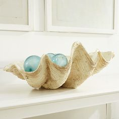 beautiful sea glass fishing floats in a large white clam shell love