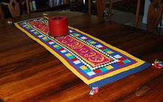 Handmade table runner in traditional applique ralli quilt design.