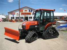 Tracks and front dozer blade on a Kubota B3030 with a cab.