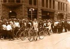 Bicycle Race -View of a group of boys on bicycles surrounded by a crowd of boys in front of the Masonic Temple at the corner of 14th and Pearl. This is possibly the Lions Club race in 1921.  REPRODUCTIONS