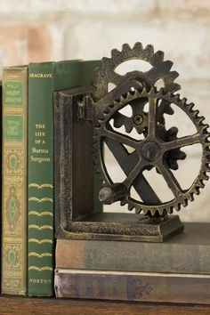 Industrial Gear Sculptural Iron Book End | With its steampunk feel and industrial-chic look, we can imagine a lot of interior design or office settings for these iron bookends. Lots of guys have a collection of books (big or small) that could be displayed in a unique way. More details here... #anniversarygifts #weddinganniversary #weddinganniversarygifts