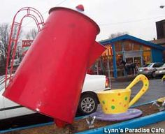 Lynn's Paradise Café, Louisville, Kentucky. A big coffee pot in front of the restaurant is 8-ft. tall, a bright red pot at ground level and features a companion coffee cup. The pot, built by the Cafe staff in 1994, operates as a fountain, pouring tap temperature water into the cup.