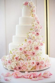 A pretty pink tiered cake gets extra beautiful with added roses.