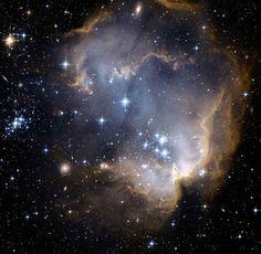 Cúmulo y Nebulosa NGC 602 (N90). Es un cúmulo estelar abierto en la cabeza de la Nebulosa del Lagarto Volador, ubicado en los bordes de la Pequeña Nube de Magallanes. Cúmulo en proceso progresivo de formación estelar desde su centro.
