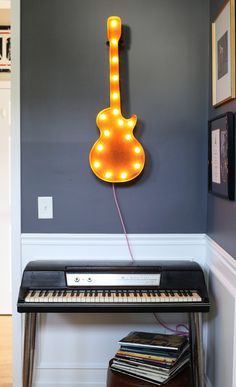 #VintageMarqueeLights Rusty guitar light hanging above a keyboard in a music room.  Looks cool against the grey wall!  www.vintagemarqueelights.com http://blog.vintagemarqueelights.com