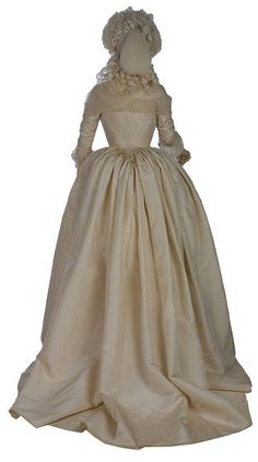 Robe, 1780-85 France, the Victoria & Albert Museum This gown demonstrates the fashionable styles in women's formal dress of the 1780s. The hoop has changed from the square shape of earlier decades to a round profile. A stomacher is no longer needed, because the gown now meets in the front. The cream silk is adorned only at the edges with an embroidered band, ribbon and a stencilled fringe. This restraint in decoration illustrates the growing influence of the Neo-classical style in textile…