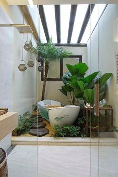 10 Bathroom Ideas That Will Make It Actually Feel Like Spring, Now  | Tropical glass bathroom with freestanding bathtub and jungle plants