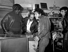 Bruce Springsteen playing pinball with Clarence Clemons, Roy Bittan + Steve Van Zandt, East Camden, New Jersey, 1978.    Photo by Frank Stefanko