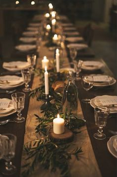 Long tables with burlap , long vines and candles