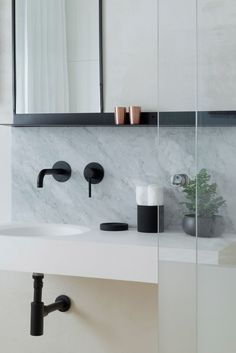 Industriële badkamer met een mix van matte zwart en wit marmer. Contrast is key!