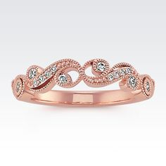 Twenty round diamonds, at approximately .18 carat total weight, accent throughout vintage-inspired swirl designs found in this ring. In addition to the diamonds, milgrain detailing also complements the vintage band. This ring measures 4mm wide and is crafted of quality 14 karat rose gold.