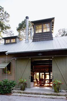 Barn Style Home. Large barn doors open to the open dogtrot entry area. (A dogtrot is an open breezeway, and dogtrot houses are common in Lowcountry.) Large screens are stashed in pockets so the entire opening can be screened, letting the breeze through without letting in the bugs.                                                                                                                                                                                 More