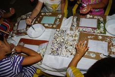 mamma Lucia insegna ai bimbi a costruire cornici decorate con i tesori del mare.