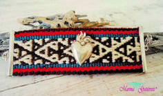 Brazalete con corazón en llamas y terminales en plata .950.  Bordado tejido en telar de cintura de la comunidad tarahumara (rarámuri) de la sierra de Chihuahua.