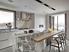 V kuchyni, která je od obývacího pokoje oddělena, je jídelní stůl, na nějž navazuje barový pult z přírodní žuly.