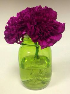 3 giant purple carnations placed in an awesome mason jar from the 99 cent store. Mason jar as vase. Purple Carnations. Green mason jar. Joker themed flowers.