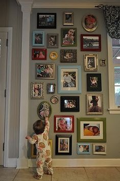 Idea for wall top of stairs as go down! Love this photo wall - did this in my upstairs hall. We call it the family wall because it is photos of our extended families. I did a mix of photo frame styles but stuck to silver and black as colors.