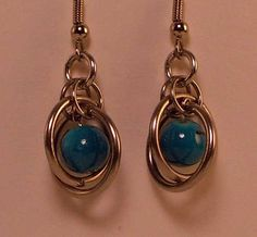 The steel and aluminum Chainmaille earrings surround blue with black glass beads. These dangle approximately 1 inch from surgical steel French hooks.  If you would like a different color bead please convo me!  If your piece ever breaks, for any reason, all you do is send it back to me and I'll fix it for no charge. If for some reason it doesn't fit, (gained x-mas weight or went to the gym?) send it back and I'll adjust it for you. My hope is you to be completely happy with your order.