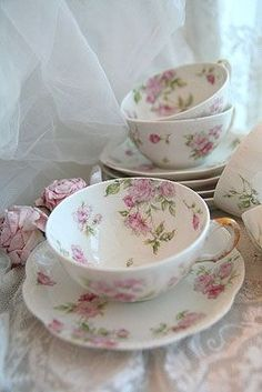 white tea cups and saucers with pink flowers