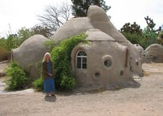 Minus the goofy little round windows and hippy chick. How I want our home - Earth bag dome home - coil pot style construction with sand bags covered with adobe Maison Earthship, Earthship Home, Casa Dos Hobbits, Earth Bag Homes, Unusual Buildings, Modern Buildings, Adobe House, Sand Bag, Natural Homes