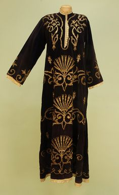 TURKISH WEDDING TUNIC, 19th C. Aubergine velvet having heavy gold metallic satin stitch embroidery with stylized carnations and scrolling foliage, lace trim at cuffs, neckline and hem, muslin lined. Bust 38, length 55. Shoulders slightly oxidized, few broken threads