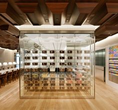 The refrigerated display case backs onto the open kitchen and separates the casual dining area of the café from its colorful retail section. Containing 56 bins of chocolate—each with a different flavor—the full-height glass unit provides a deliciously transparent foil for the rich walnut ceiling above.