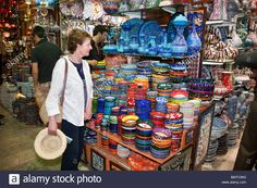 Download this stock image: Tourist looking at ceramic pottery for sale in the Grand Bazaar, Istanbul, Turkey - BMTCWG from Alamy's library of millions of high resolution stock photos, illustrations and vectors.