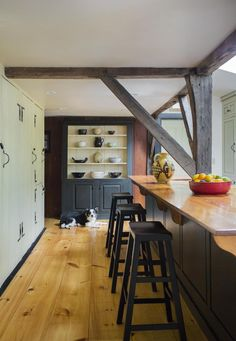 "From a rehabbed ""First Period"" Colonial home in Ipswich, Massachusetts: ""The kitchen has an island topped by re-purposed barn wood."""