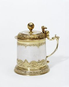 Augsburg goldsmiths quickly adopted the Régence style from Parisian ornament prints and produced elegant designs of their own. This tankard, a common choice of gift in southern Germany, is decorated with delicately chased and engraved borders of strapwork, scrolls, fruits and lambrequins (draped cloths).