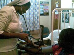 Here Sister Mary attends to a sick boy in Nigeria.