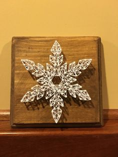 This would make a great gift or beautiful winter decor for your own home! This hand-crafted string art snowflake is made on stained wood with