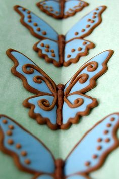 Royal icing butterfly - the wings are piped on a flat surface, then placed on the V fold to pipe the center, so they have raised wings. Clever!