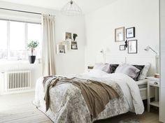 intérieur scandinave blanc et épuré dans la chambre à coucher avec literie en blanc et beige