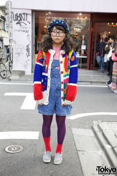 This cute girl with large glasses, pigtails and a polka dot cap is Seira, a 16-year-old student. She's wearing short denim overalls from Spinns, which along with Panama Boy is one of her favorite shops. She's also wearing a red denim shirt, purple tights and red socks. Her bright sweater features color blocking and embellished buttons. Seira is carrying a Lego rucksack that looks like a big yellow Lego block. Her slip-on sneakers are from X-Girl. She told us her favorite music is by Bump of…