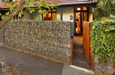 Gabion stone fence contrasting with plant fence...