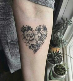 Heart-shaped flower tattoo inked on the left inner arm