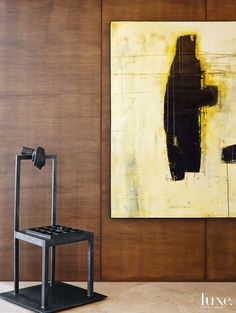 An abstract painting by Drew Harris pops against the sycamore millwork in the dining room, forming an artful vignette along with a cast-bronze chair by Spanish artist Francisco Aparicio Sanchez.