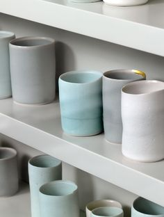 "Ceramic cups by British ceramic artist and author EDMUND DE WAAL, who was born in England but also trained in Japan. Most of his work consists of cylindrical porcelain pots with pale celadon glazes. He believes that the East and West may meet in porcelain; for example, that ""there the ethos of China's medieval Sung Dynasty may encounter the modernist ethos of the Bauhaus."""