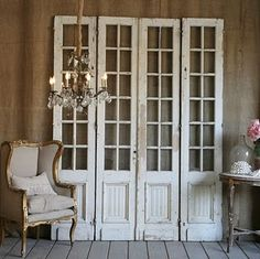 elegant tall small glass pane old wooden panel doors..shabby chic white finish..used as wall decore in living room..