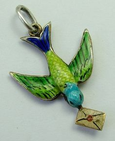 An Edwardian c1905 silver gilt and guilloche enamel puffed charm of a bird carrying a letter.