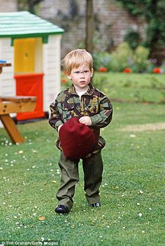 Pictured, Prince Harry plays in the grounds of Highgrove dressed in a Parachute Regiment u...
